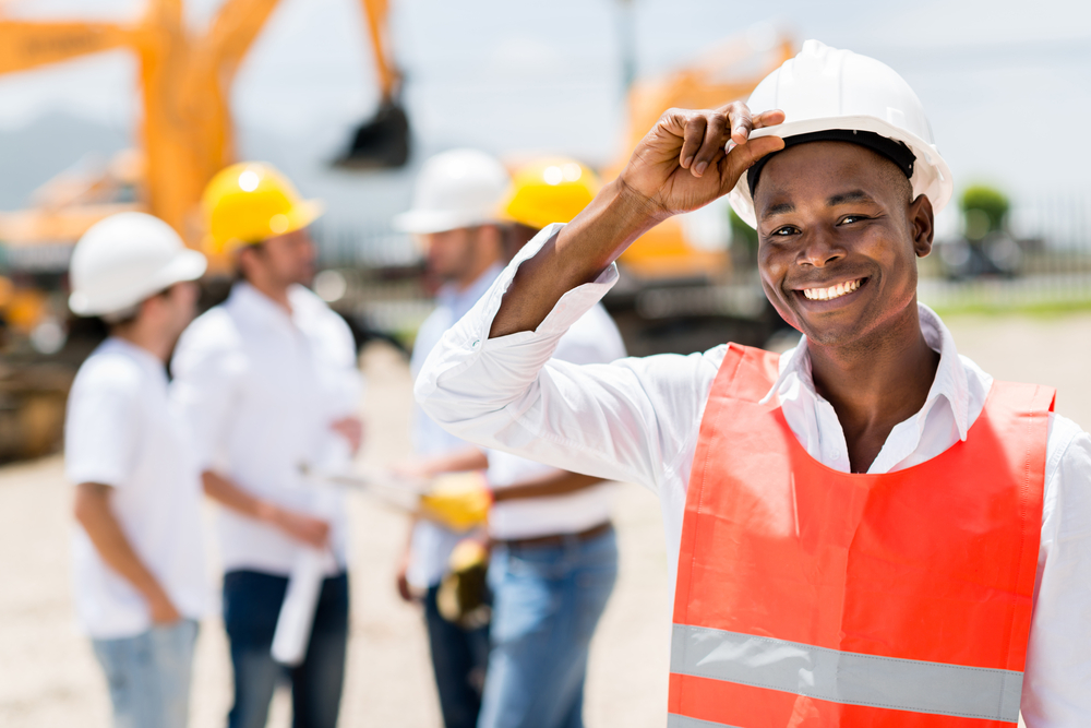 Happy male architect at a building site wearing a helmet