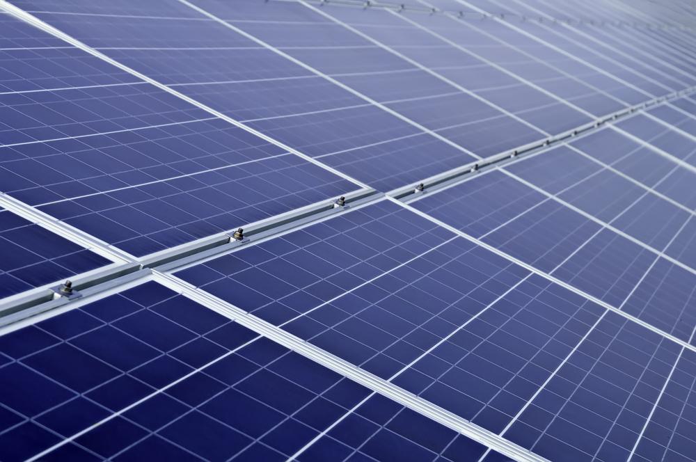 Long array of solar panels in bright sunlight